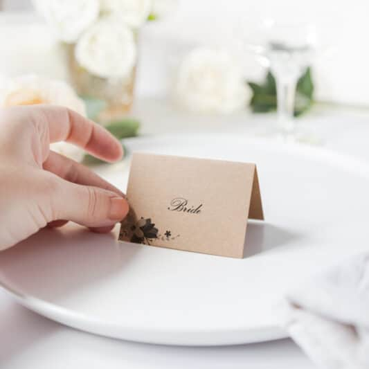 Hand putting down folded brown card place name onto plate