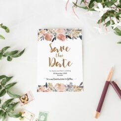 save the date card next to flowers and pen