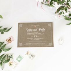 Rustic country invite next to engagement ring