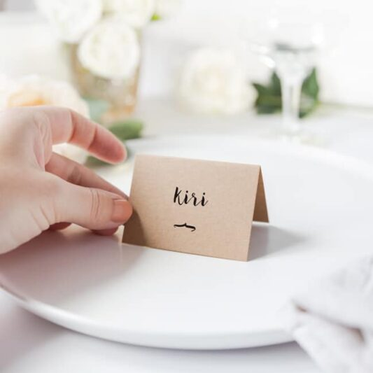 hand holding kraft folded card with printed black guest name