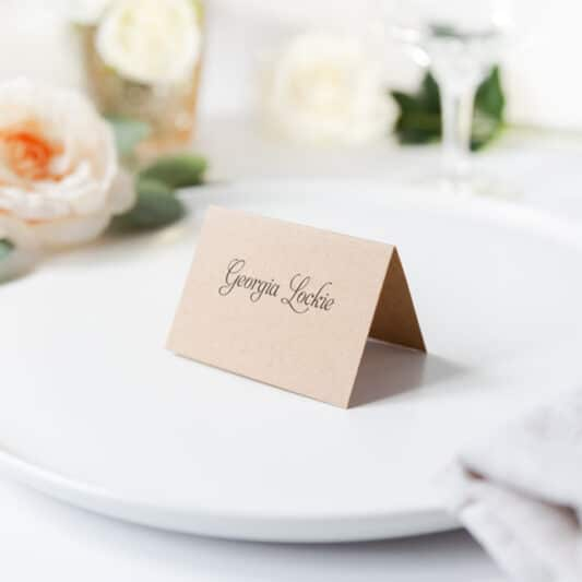 folded kraft brown card with guest name sitting on wedding reception table on a plate