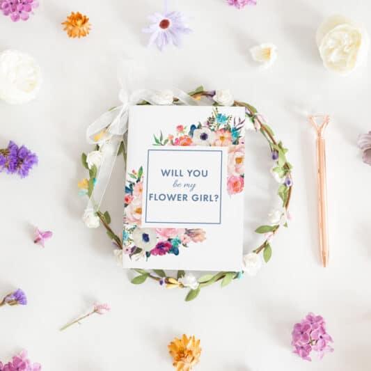 front of flower girl card sitting on flower wreath headband