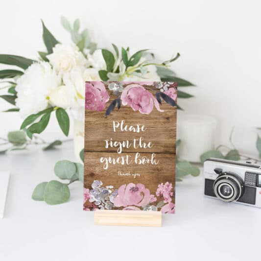 sign on small wooden stand next to guestbook with black pages